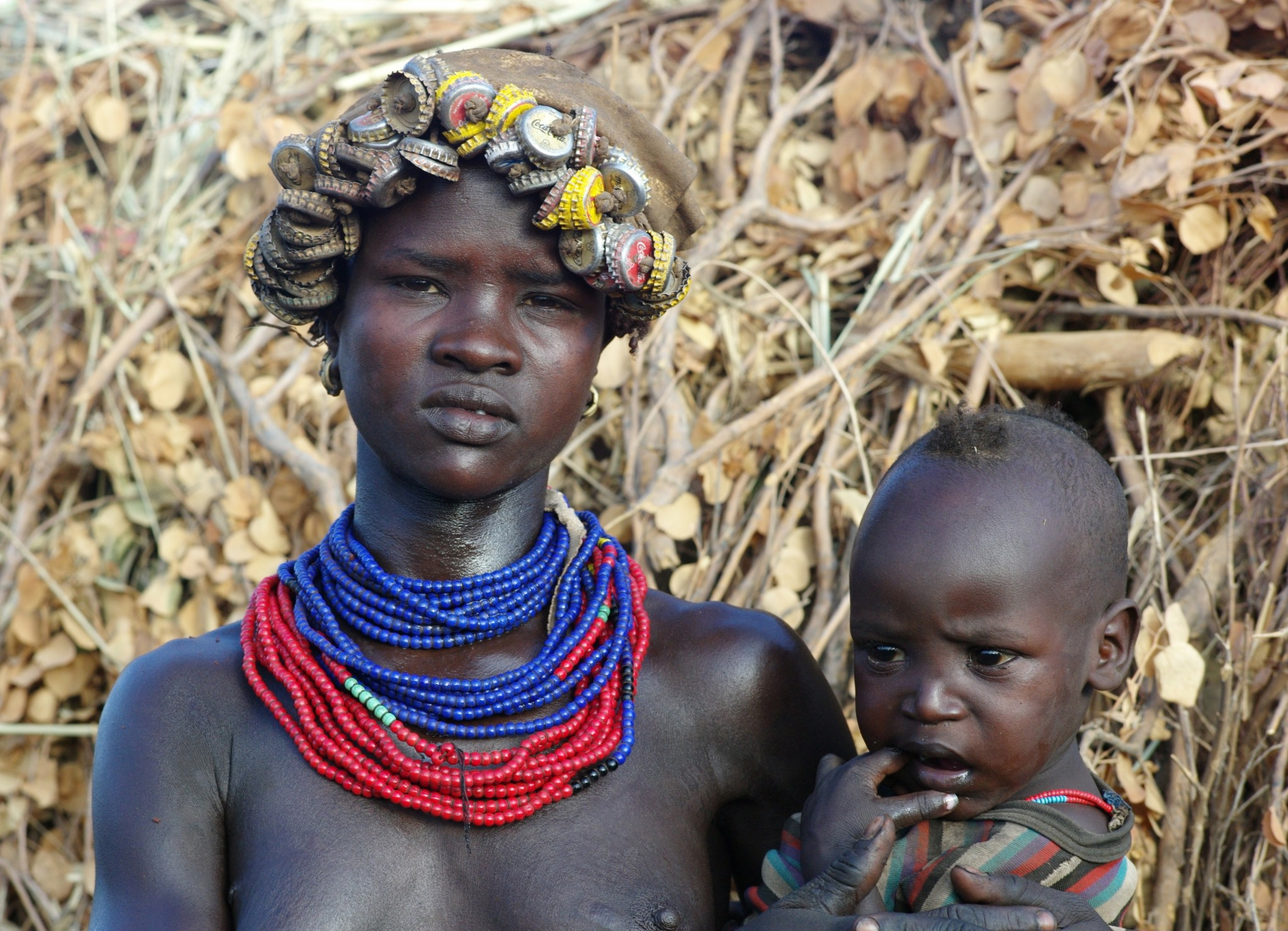 women tribe with bottle caps as a hat